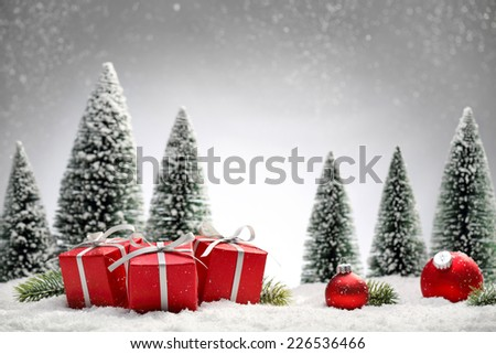 Red Christmas balls,gift boxes and fir tree on snow - stock photo