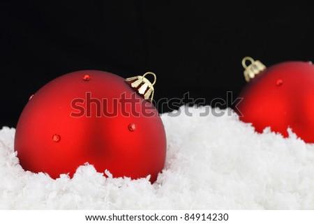 Red Christmas balls on snow - stock photo