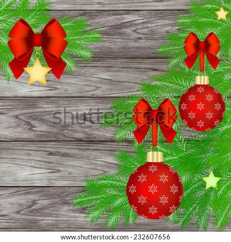 Red Christmas balls with red bow hanging on Christmas tree against a wooden background. - stock photo