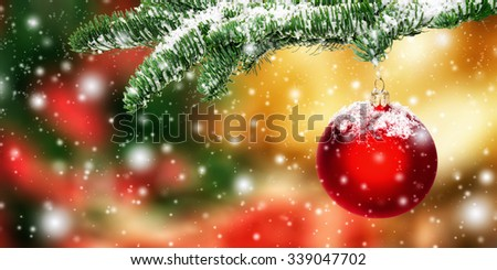 Red Christmas bauble in snow hanging from a fir branch, with colorful blurred background - stock photo