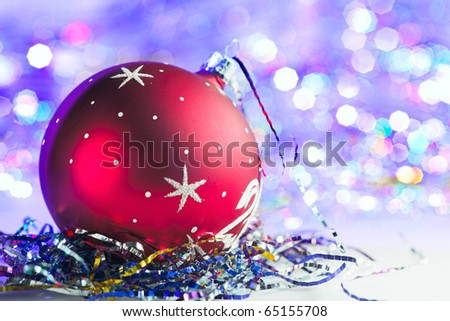 Red Christmas bauble with blured lights in background - stock photo