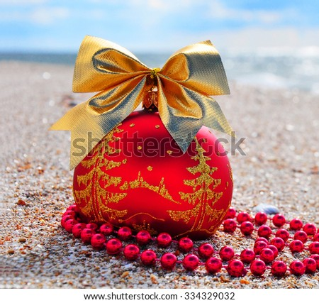 Red christmas bauble with golden bow and beeds on sand against blue ocean - stock photo