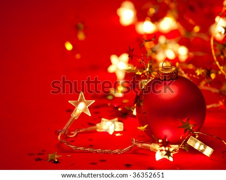 Red Christmas bauble with star-shaped lights and tinsel on red background, shallow DOF - stock photo