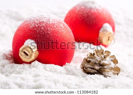 Red christmas baubles and cone on snow - stock photo