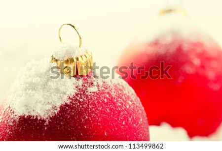 Red christmas baubles on snow - stock photo
