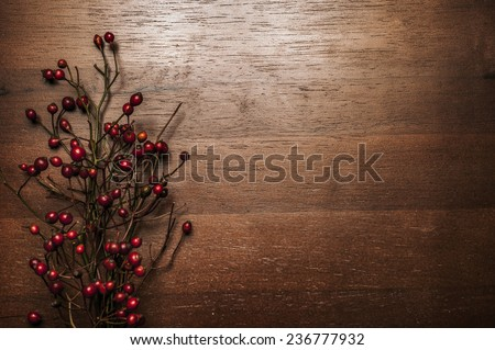 Red Christmas berries on wooden background - stock photo