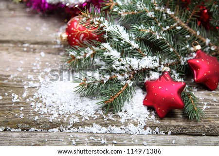 Red Christmas decoration on spruce branches with snow - stock photo