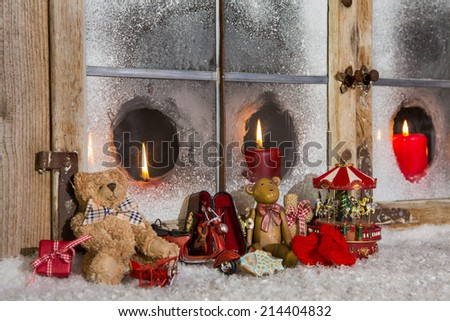 Red christmas decoration with candles and old children toys on the background. - stock photo