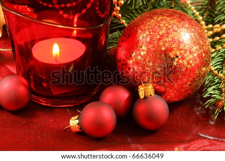 Red Christmas decoration with glass balls, fir branch and candle - stock photo