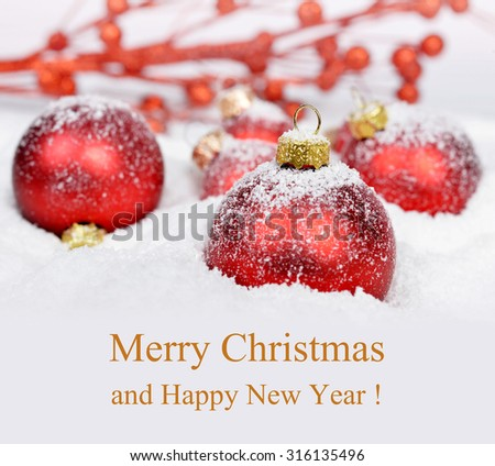Red Christmas decorations in snow. Merry Christmas card.