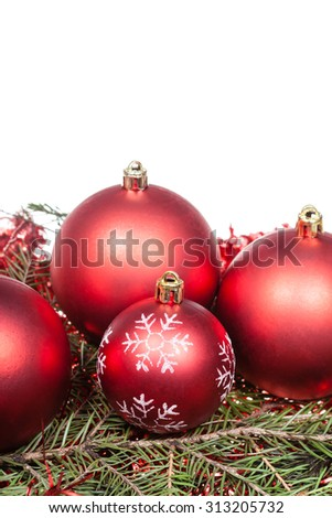 red Christmas decorations on green spruce tree branch isolated on white background