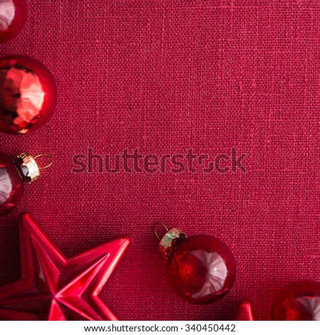 Red christmas decorations (stars and balls) on red canvas background. Merry christmas card. Winter holidays. Xmas theme. Happy New Year. - stock photo