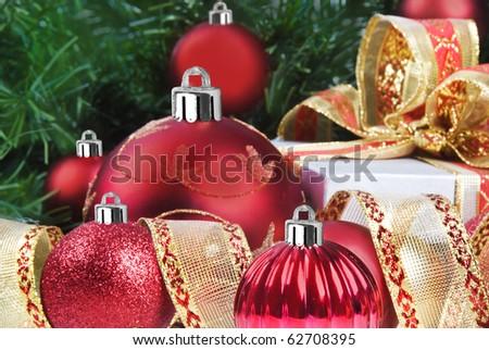 Red christmas decorations under a christmas tree in low light with high contrast - stock photo