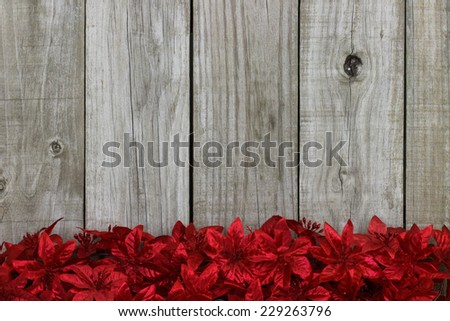 Red Christmas garland flower border against rustic antique wooden background - stock photo