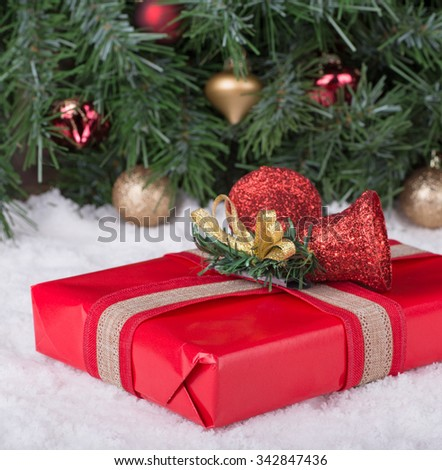 Red Christmas gift box on snow with holiday background - stock photo