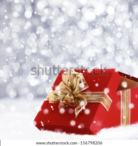 Red Christmas gift box with its lid propped at an angle in front to display the beautiful shiny metallic gold ribbon with falling winter snowflakes and copyspace for your greeting or wishes - stock photo