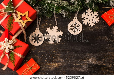 Red Christmas gift boxes in rustic style with holiday decorations, selective focus