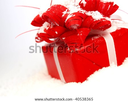 Red Christmas gift covered with snow