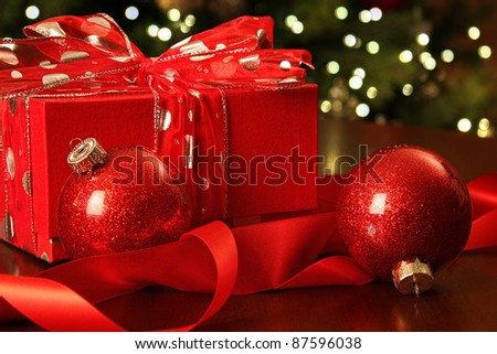 Red Christmas gift with ornaments in front of tree - stock photo