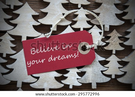 Red Christmas Label With Ribbon On Wooden Christmas Trees Background. Vintage Or Rustic Style. Label With English Text Believe In Your Dreams For Christmas Or Season Greetings.Close Up Or Macro - stock photo