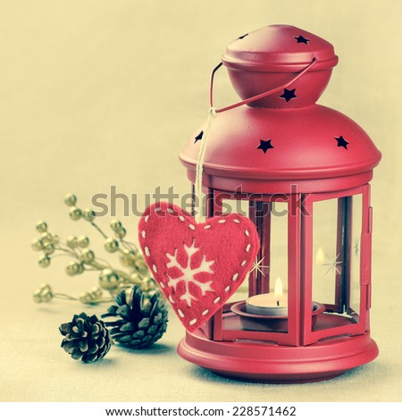 Red Christmas lantern with a decorative felt heart with a snowflake and pine cones at the background with retro vintage filter effect and copy space - stock photo
