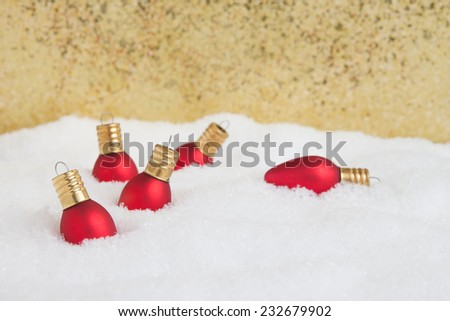Red Christmas light ornaments in the snow with gold  glitter background - stock photo