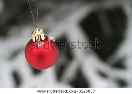 Red Christmas ornament hanging outside in the snow - stock photo