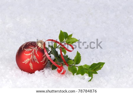 red Christmas ornament with holly and ribbon on a bed of snow - stock photo
