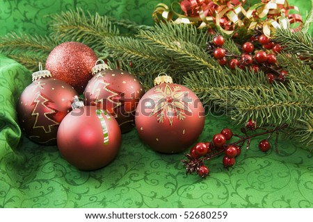 red Christmas ornaments on a green background with fir branch and holly accents - stock photo