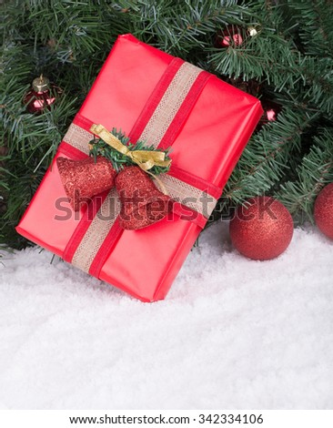 Red Christmas present on snow against a Christmas tree - stock photo