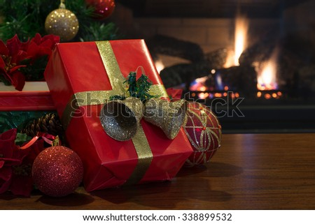 Red Christmas presents with decorations and fireplace in background