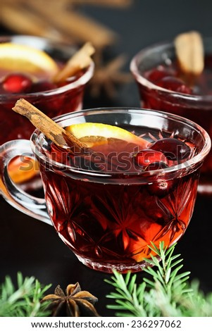 Red Christmas punch / drink with cinnamon, orange slices, anise and fresh cranberries over a dark background. Extreme shallow depth of field with selective on cup in foreground. - stock photo