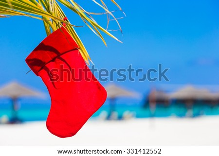 Red Christmas stocking on palmtree at tropical beach - stock photo