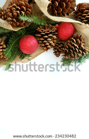 Red Christmas Tree ornaments, natural pine cones, evergreen branches, and burlap Holiday ribbon are creating a decorative frame, isolated on a blank white background with copy-space.