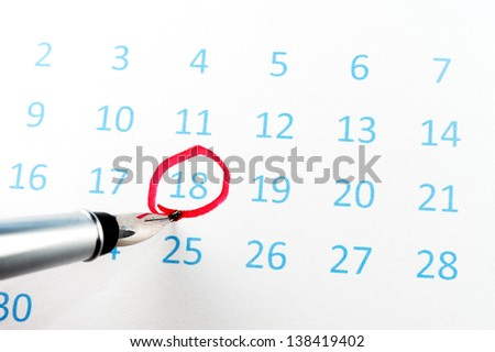 Red circle marked on a calendar with a pen - stock photo