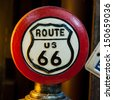 Red Circular of Route 66 Sign (orange light from left side) - stock photo