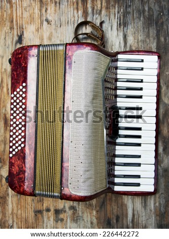 Red classic children accordian on wooden background - stock photo