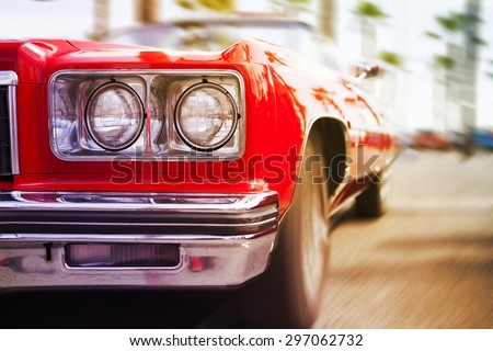 Red classic sports car driving fast, with motion blur background. Close up view. - stock photo