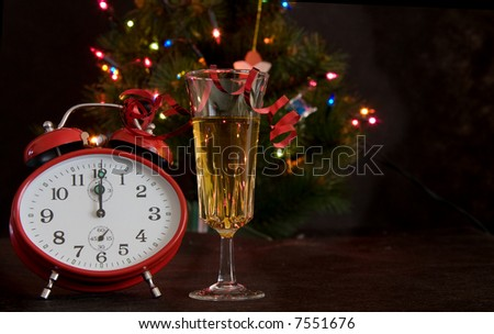 red clock and glass of champagne on Christmas lights background