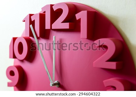 Red clock showing five to midnight on the face - stock photo