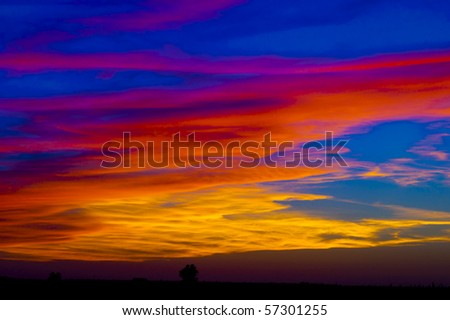 Red clouds over a farm - stock photo