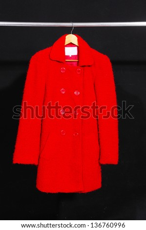 Red coat hanging on hanger-black background - stock photo