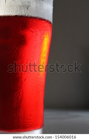 Red cocktail in a glass on a gray background