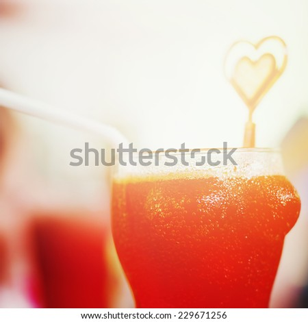 Red cocktail in funny glass in the shape of female breast. Instagram vintage effect. - stock photo