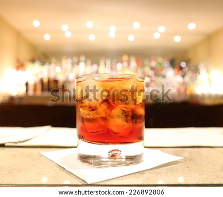 red cocktail in the foreground with counter bar with bittles in the background - stock photo