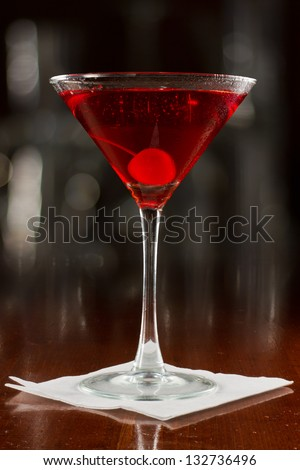 red cocktail served on a busy bar top garnished with a cherry - stock photo