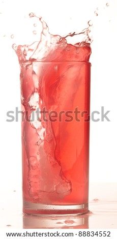 red cocktail splashing into glass on white background