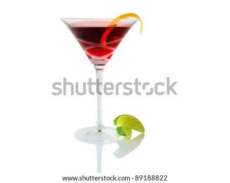Red cocktail with lemon rind spiral garnish and lime wedge, isolated - stock photo