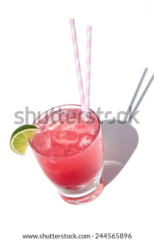 Red cocktail with lime garnish on white background.