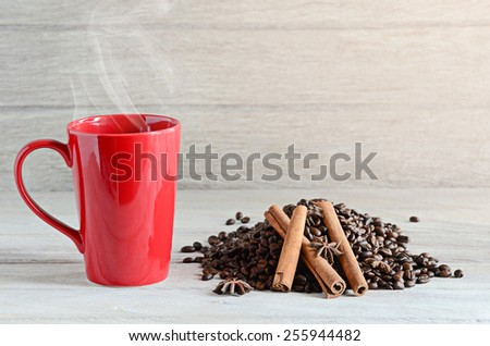 Red Coffee cup and coffee beans on wooden table - stock photo